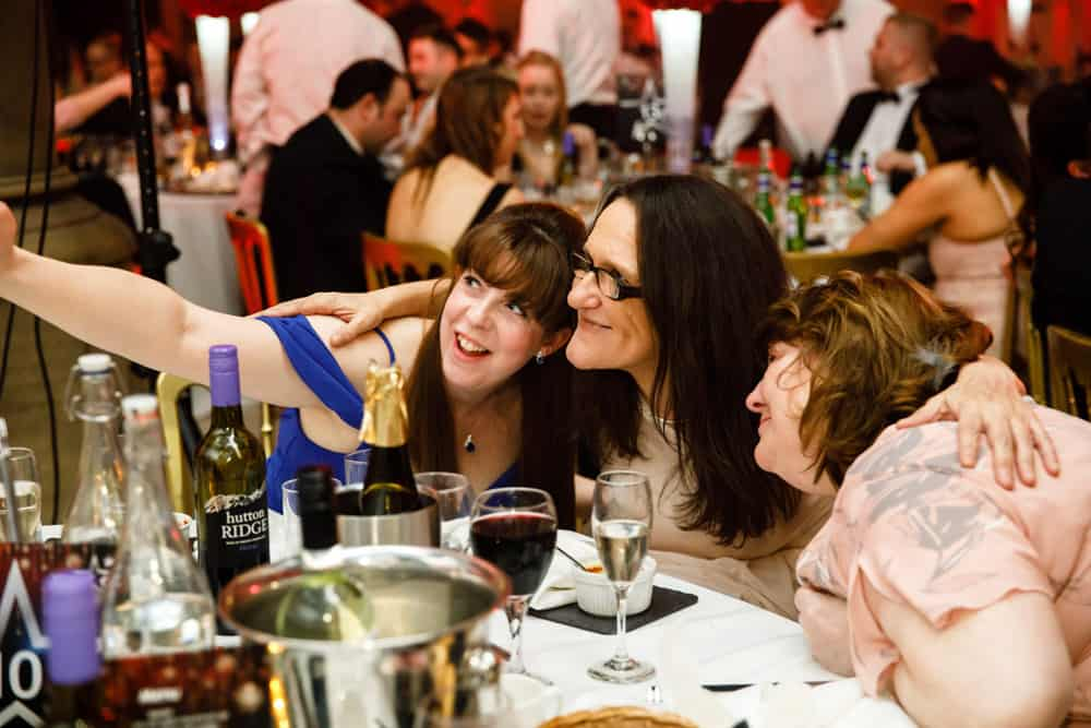 Guests taking selfies at their awards dinner