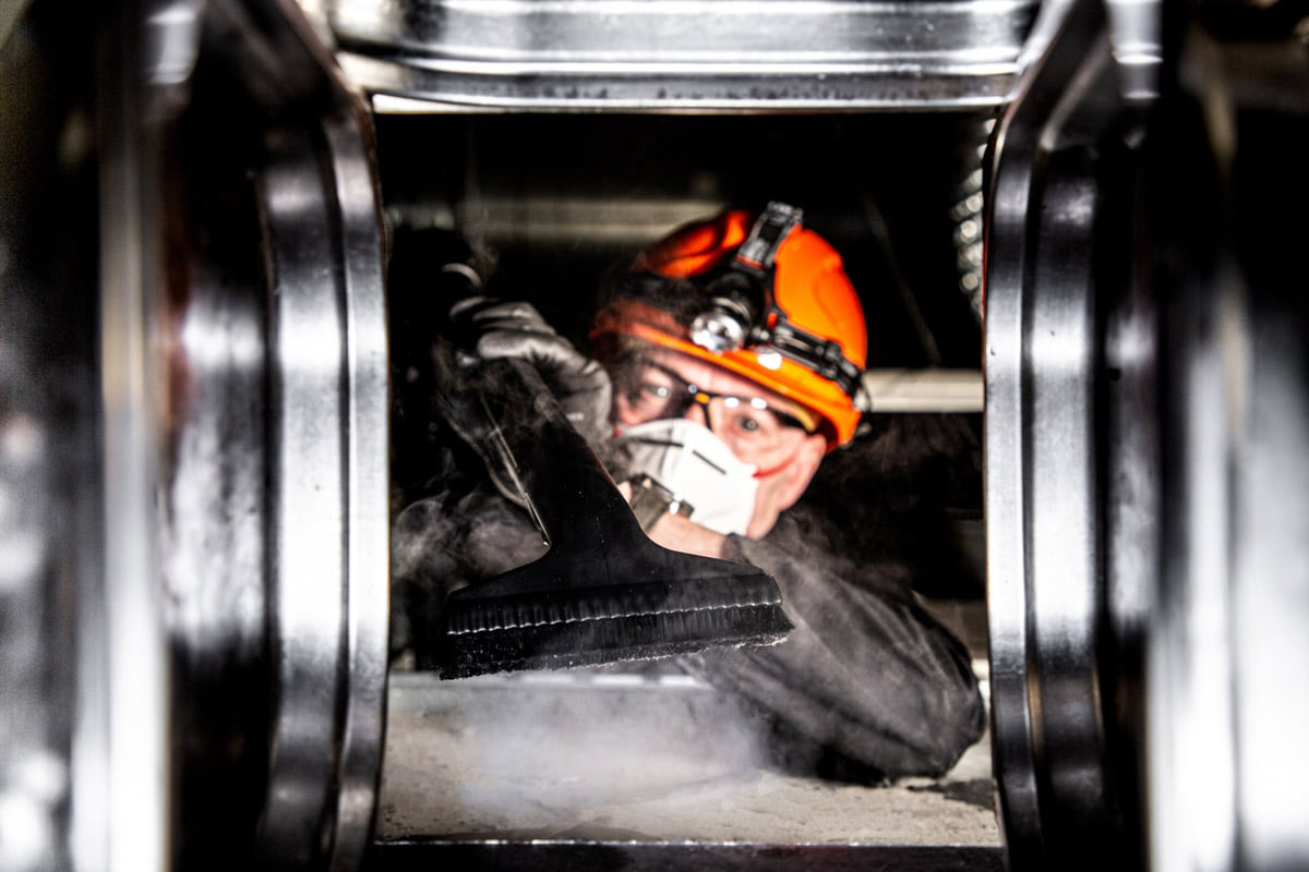 Commercial Photographer Manchester photo of worker cleaning a duct
