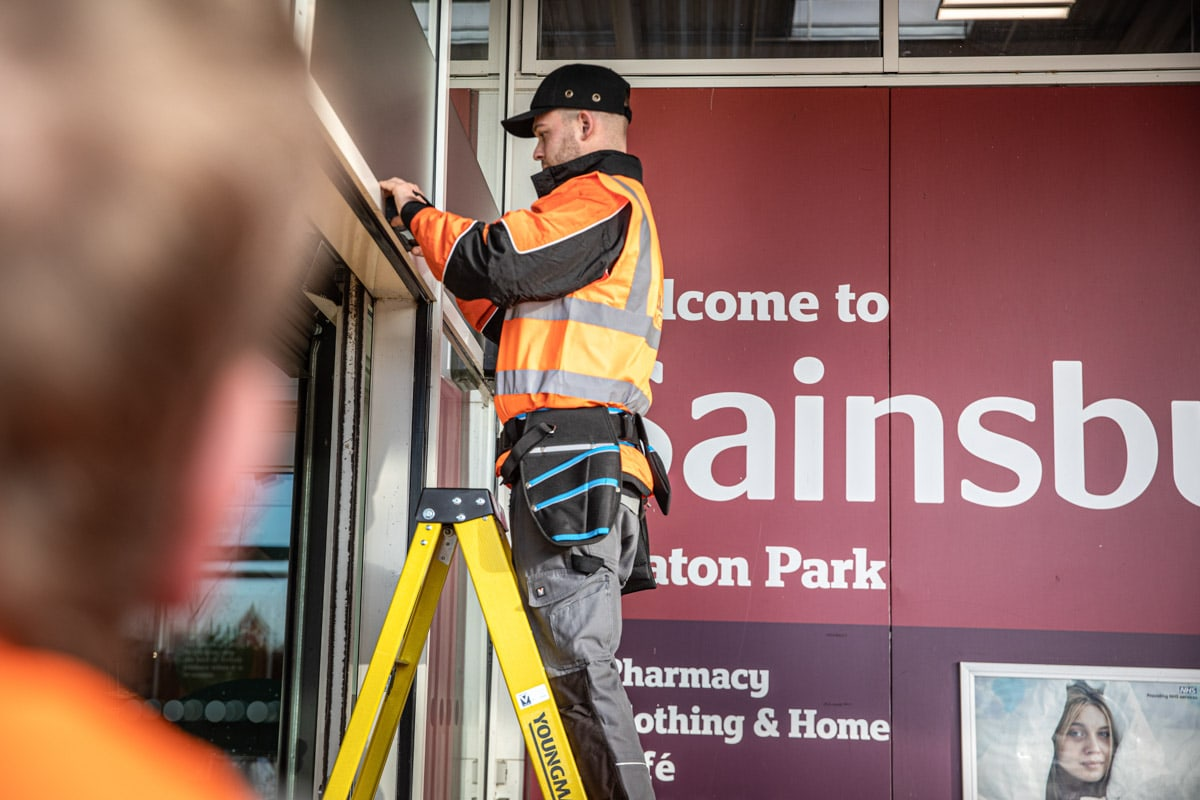 Commercial Photographer Manchester photo of men fixing door at sainsburys